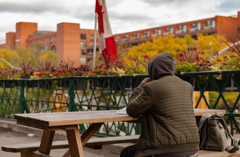 Rear view of person sitting on picnic table against building