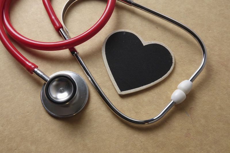 MEDICAL CONCEPTUAL WITH STETHOSCOPE ON A BROWN BACKGROUND Close-up Diagnostic Medical Tool Emotion Headphones Healthcare And Medicine Heart Shape High Angle View In-ear Headphones Indoors  Listening Love Medical Equipment Medical Exam Medical Instrument Medical Supplies Music No People Pulse Trace Stethoscope  Still Life Table