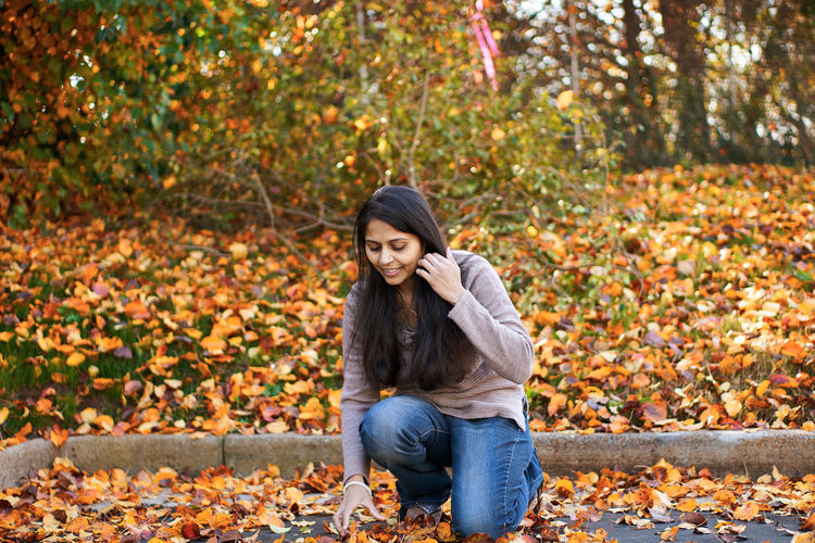 Woman kneeling on leaves during autumn