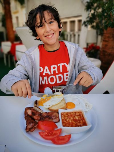 Portrait of a smiling boy having english breakfast food in an outside restaurant