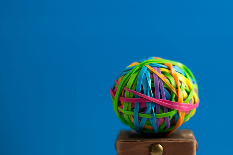Low angle view of multi colored ball against blue background