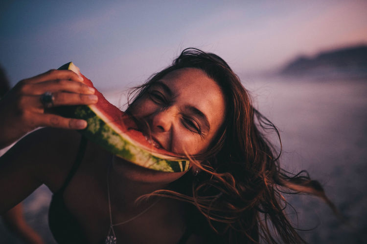 Portrait of woman eating watermelon at beach against sky