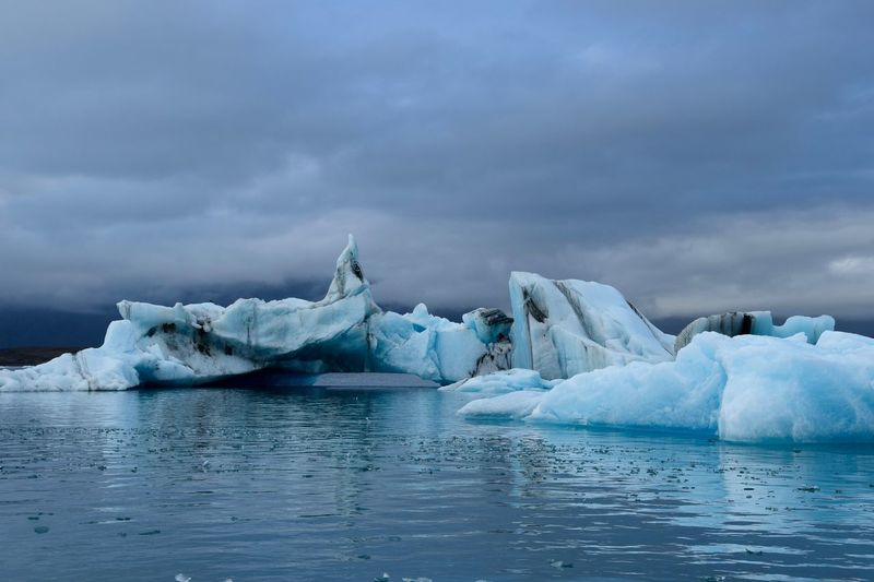 Tranquil scene with icebergs against cloudy sky