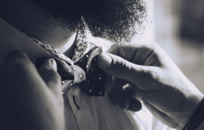 Cropped image of person adjusting bowtie of man