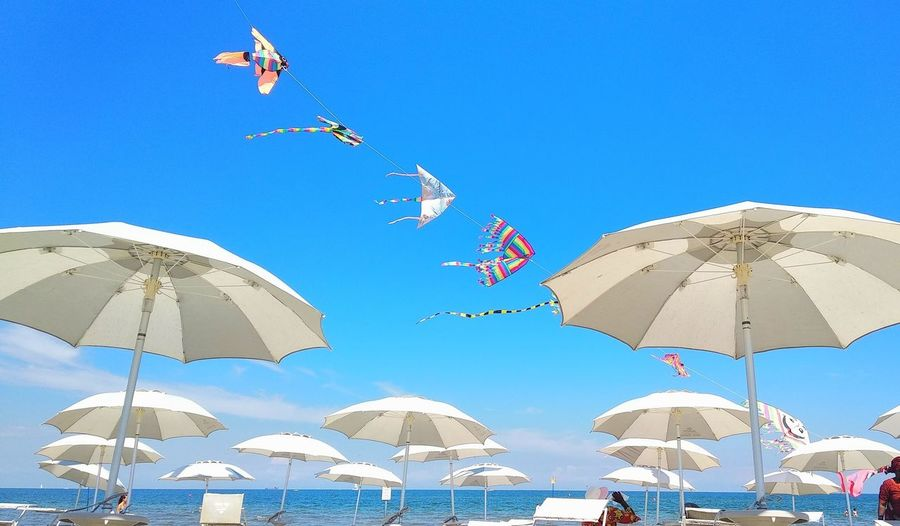 Low angle view of umbrellas hanging on beach against clear blue sky