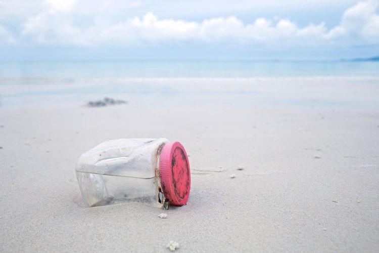 Pink umbrella on beach against sky