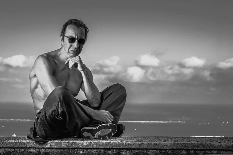 Shirtless mature man sitting against sea and sky