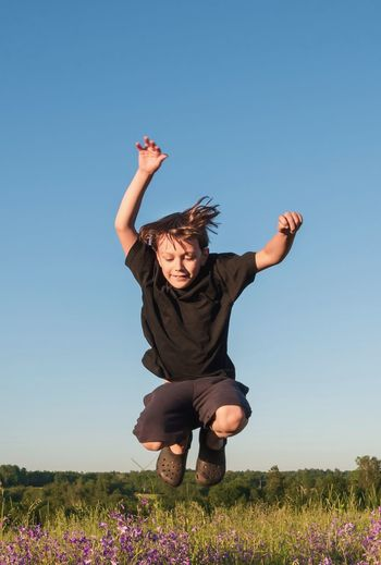 Full length of child jumping on field against clear sky