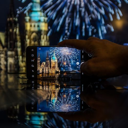 Midsection of person photographing illuminated smart phone at night