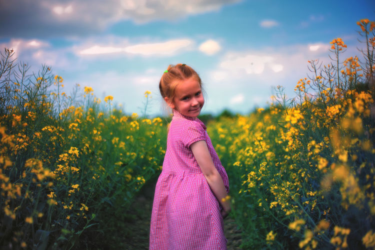Side view portrait of girl standing amidst yellow flowers blooming on rape field