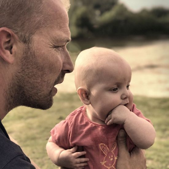 Mid Adult Men Togetherness Father Family Family With One Child Real People Baby Mid Adult Love Leisure Activity Bonding Childhood Babyhood Lifestyles Focus On Foreground Day Side View Outdoors Close-up