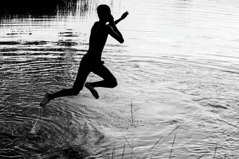 Silhouette Boy Jumping In River