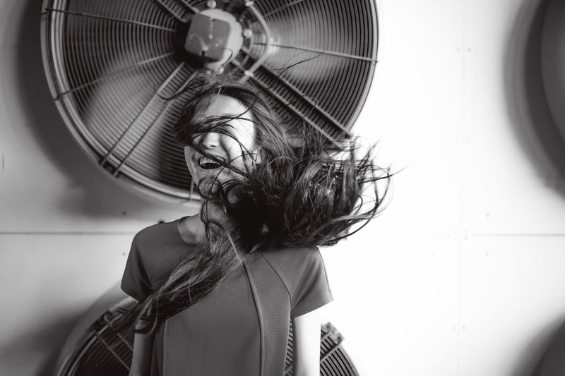 Young woman standing by fans