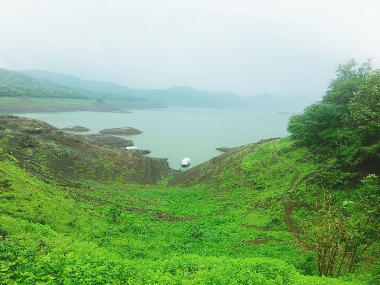 nature, green color, beauty in nature, water, tranquil scene, tranquility, scenics, lake, mountain, high angle view, tree, outdoors, growth, no people, day, grass, plant, fog, landscape, sky