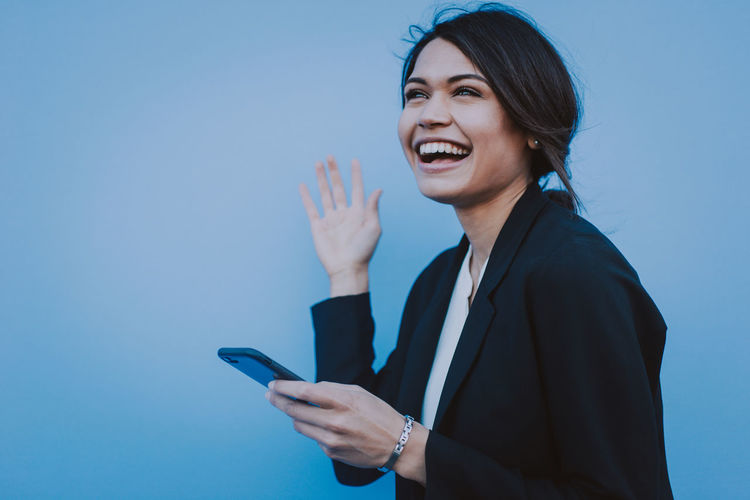 Cheerful young businesswoman using mobile phone while standing against blue background
