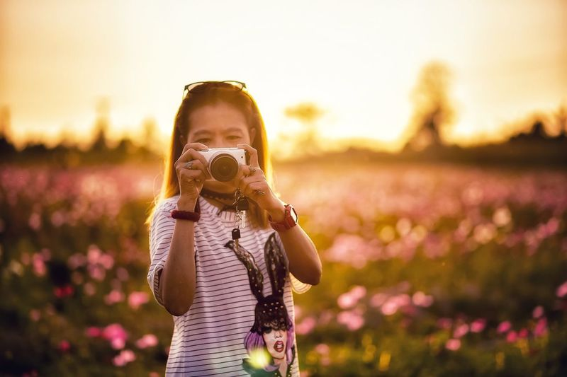 Woman Photographing With Camera While Standing On Field During Sunset