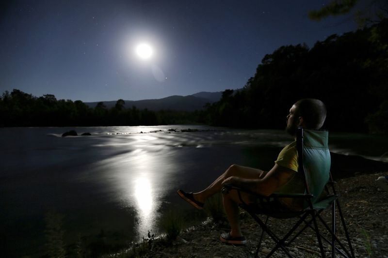 Man sitting on lakeshore against sky at night
