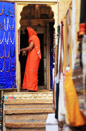 Woman Wearing Orange Sari Standing At Jewelry Store