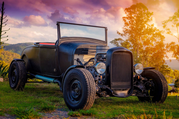 Vintage car parked at grassy area against cloudy sky