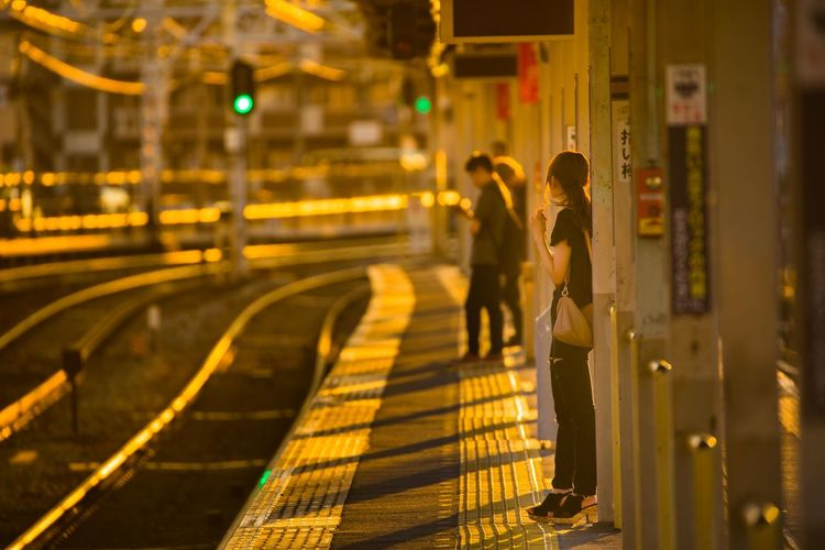 People Standing On Railroad Station At Night