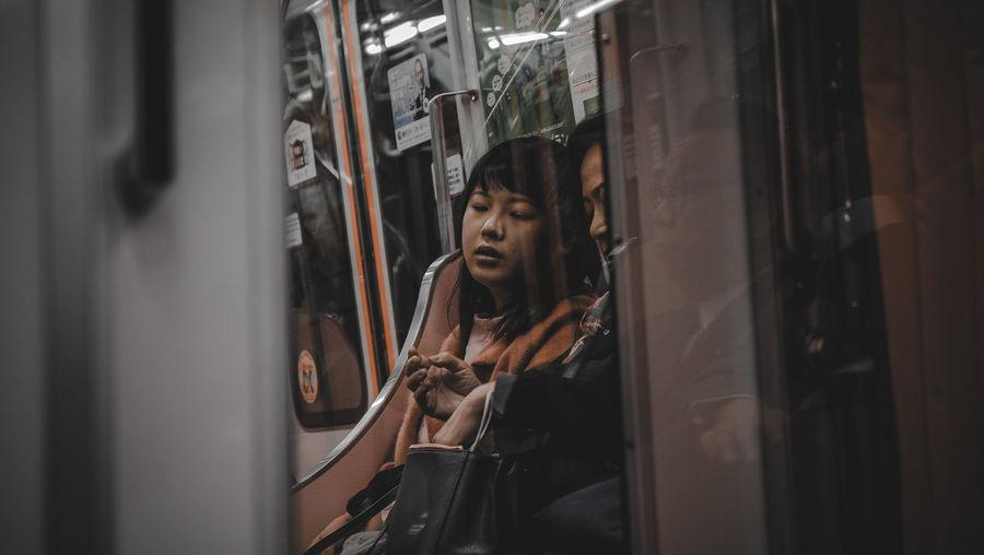 People sitting in train seen through window