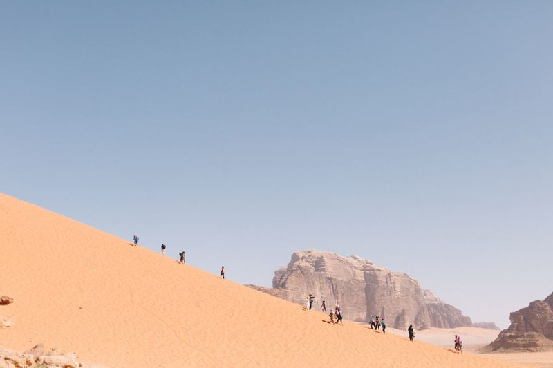 Group of people on land against clear sky