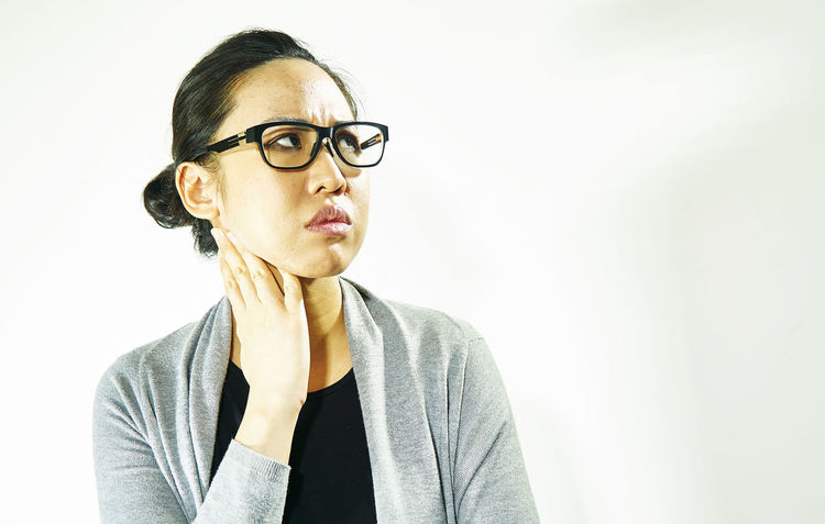Asian woman, Puzzled woman Doubt Expectations Suspicion Unhappy Wait Worried Adult Await Beautiful Woman Close-up Depressed Distrust Doubts Expectation Eyeglasses  One Person People Portrait Sad State Of Mind  Studio Shot Troubled White Background Young Adult