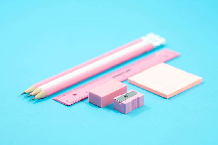 Close-up of school supplies against blue background