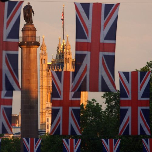 Low angle view of british flag against palace of westminster
