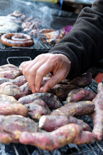Cropped hands of person preparing food on barbecue grill