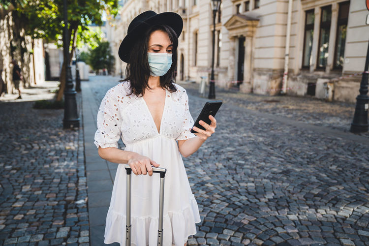 Young woman using phone while standing on street
