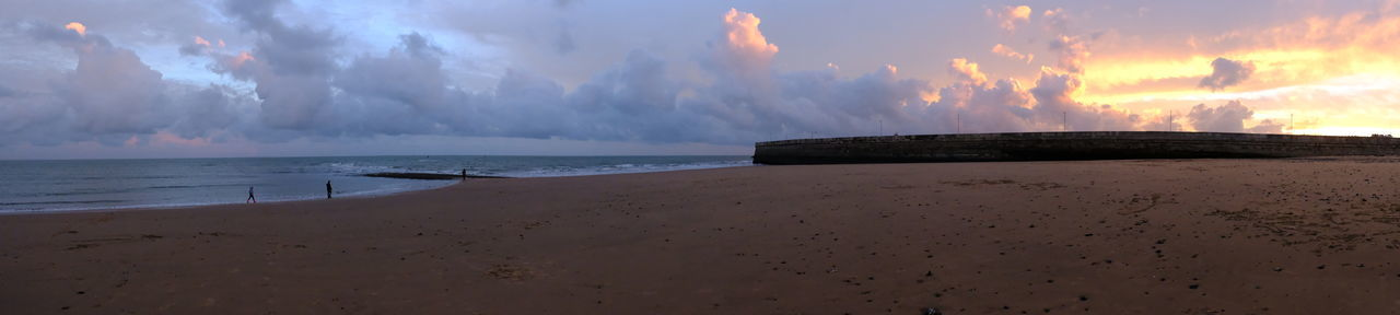 Panoramic view of calm beach against cloudy sky