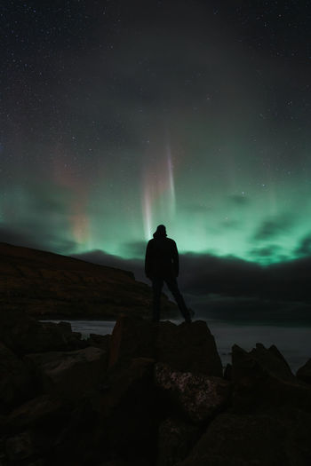Rear view of man standing on rock at night
