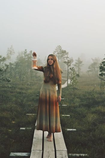 Mystical Scenery Nature Swamp Photoshoot Fall Sunrise Long Hair Looking Away Candle Cloud - Sky Warm Clothing Young Women Women Portrait Full Length Fog Tree Cold Temperature Sky Posing Natural Beauty Fashion Model Boho Foggy Hippie Dress