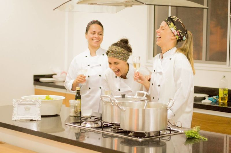 Female chefs laughing while having champagne in commercial kitchen