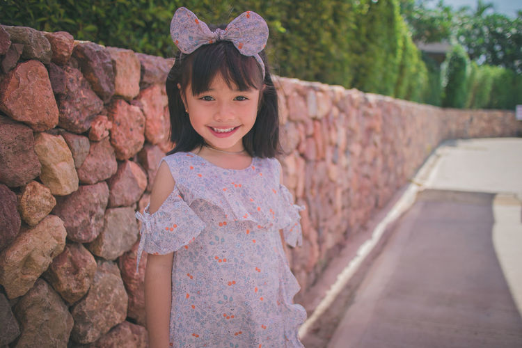 Portrait of a smiling girl standing against stone wall
