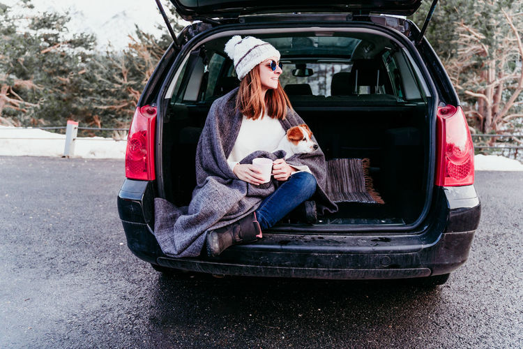 Woman holding mug sitting with dog in car trunk