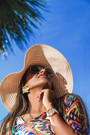 Low angle view of woman wearing sunglasses against clear sky