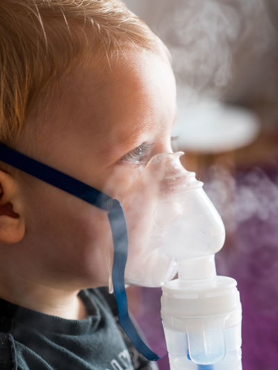 Close-up of cute baby boy taking steam at home