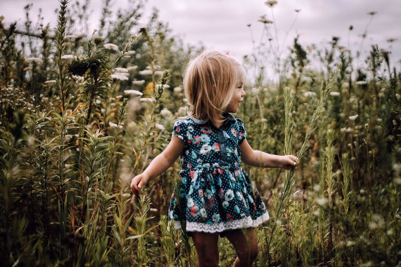 Field of flowers Growth Field Real People Girls Crop  Agriculture One Person Cereal Plant Plant Childhood Nature Rural Scene Blond Hair Lifestyles Outdoors Day Standing Landscape Sky Wheat