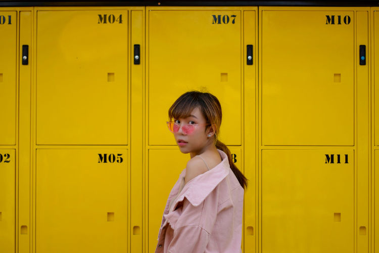 Side View Portrait Of Young Woman Standing By Yellow Doors