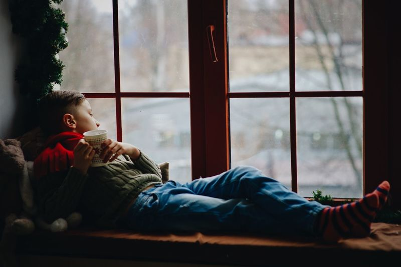 Children on Christmas Day Child Childhood Day Glass - Material Indoors  Lifestyles Looking Looking Away Males  Nature One Person Plant Real People Relaxation Sitting Transparent Warm Clothing Window Winter