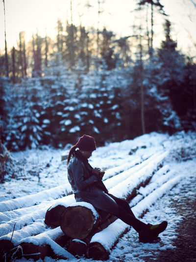 Side view of young woman sitting on snow covered log in forest during sunset