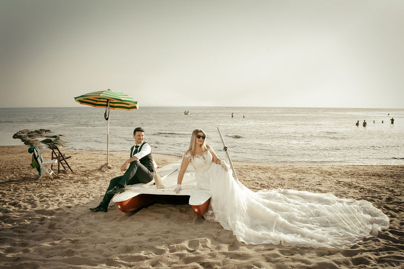 Adult Beach Bride Celebration Couple - Relationship Event Full Length Horizon Horizon Over Water Land Life Events Love Married Newlywed Outdoors Positive Emotion Sand Sea Water Wedding Wedding Dress Wife Women Young Adult Young Women