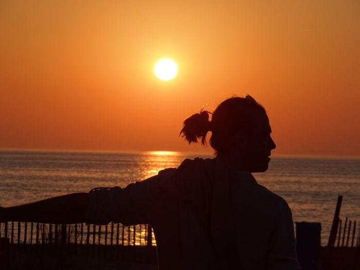 Silhouette man looking at sea against orange sky
