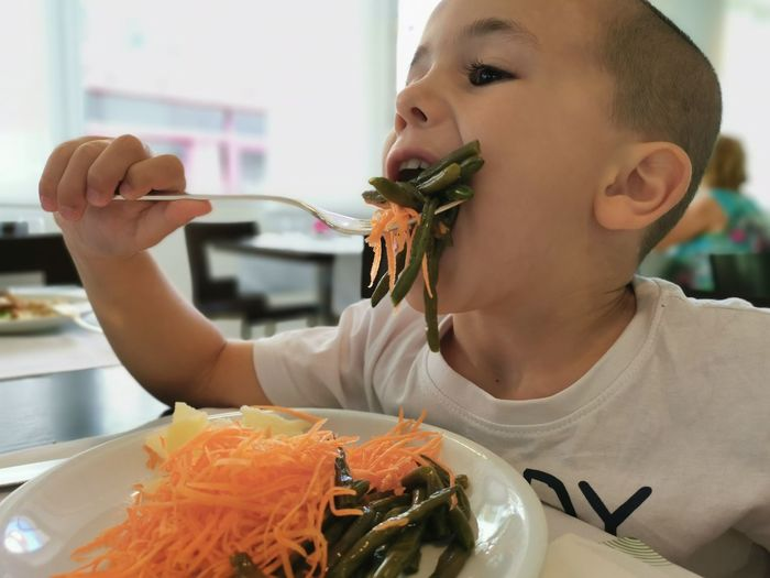 Close-up of boy eating salad in restaurant