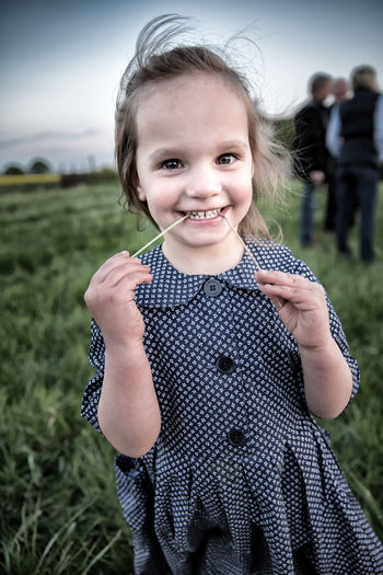 Portrait Of Smiling Girl Standing On Grassy Field