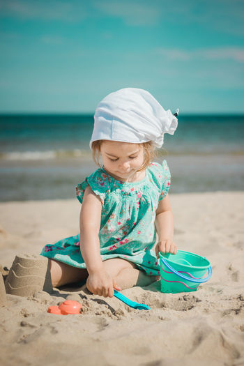 Full length of girl making sandcastles while sitting on beach