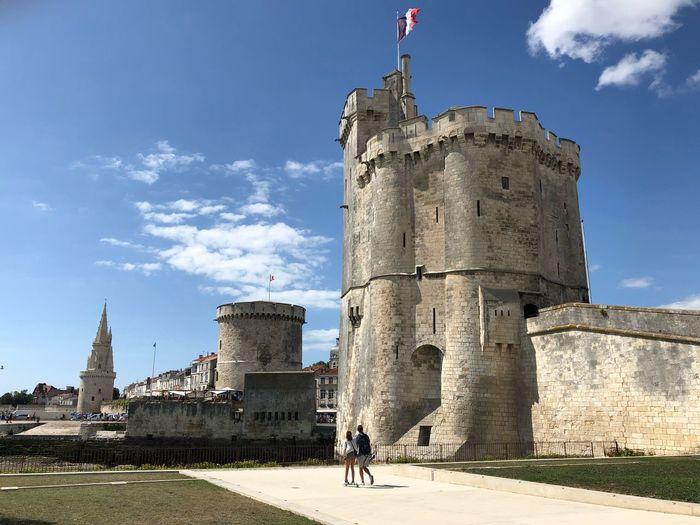 Friends walking by castle against sky