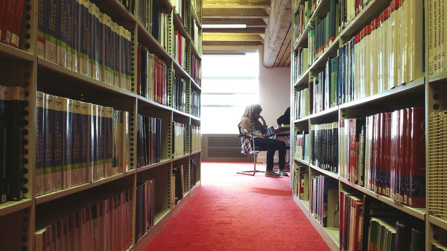 Full length of woman reading book in library